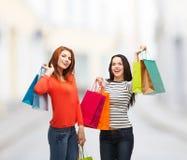 2 усмехаясь девочка-подростка с хозяйственными сумками Стоковая Фотография