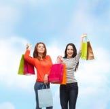 2 усмехаясь девочка-подростка с хозяйственными сумками Стоковое фото RF