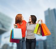 2 усмехаясь девочка-подростка с хозяйственными сумками Стоковые Изображения