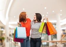 2 усмехаясь девочка-подростка с хозяйственными сумками Стоковые Фото