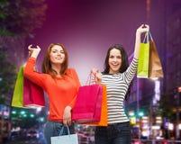 2 усмехаясь девочка-подростка с хозяйственными сумками Стоковые Фотографии RF
