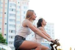 Усмехаясь девочка-подростки ехать велосипеды в городке Стоковое фото RF