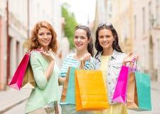 Усмехаясь девочка-подростки с хозяйственными сумками на улице Стоковое фото RF