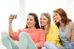 Усмехаясь девочка-подростки с smartphone дома Стоковые Фото