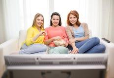 Усмехаясь девочка-подросток 3 смотря ТВ дома Стоковые Фото