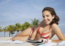 Усмехаясь девочка-подросток с кассетой на пляже Стоковые Фото