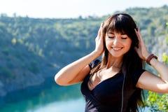 Усмехаясь девушка брюнет с длинными волосами слушая музыка на Стоковые Изображения