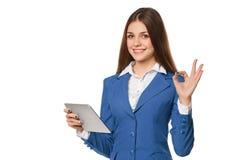 Усмехаясь девушка в голубом костюме используя показ таблетки одобряет знак Женщина при ПК таблетки, изолированный на белой предпо Стоковое Фото