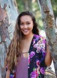 Усмехаясь девушка в деревьях стоковые фото