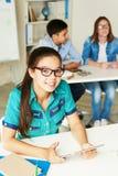 Усмехаясь девушка в классе Стоковые Изображения RF