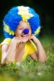 Усмехаясь девушка в парике клоуна с голубым носом лежит на зеленой траве Стоковые Фотографии RF