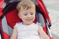 Усмехаясь девушка в прогулочной коляске Стоковое фото RF