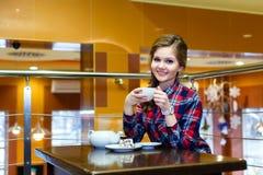 Усмехаясь девушка в чае рубашки шотландки выпивая в кафе Стоковая Фотография