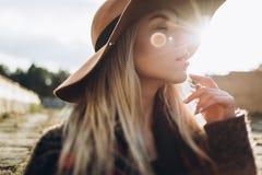 Усмехаясь девушка в шляпе идя старые улицы стоковые фотографии rf