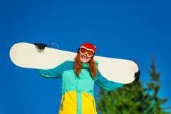 Усмехаясь девушка в лыжной маске держа сноуборд Стоковые Изображения