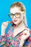 Усмехаясь девушка в Eyeglasses представляет в студии смотря камеру Портрет смешной белокурой женщины с Ponytail Стоковые Изображения RF