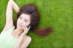 Усмехаясь девушка лежа вниз на луге и говорить Стоковые Фотографии RF