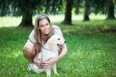 Усмехаясь девушка держа ее собаку стоковое фото