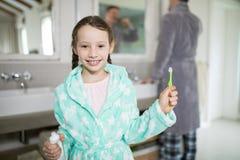 Усмехаясь девушка держа зубную пасту и зубную щетку в ванной комнате Стоковое Изображение RF