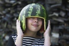 Усмехаясь девушка держа hemlet дыни на ее голове Стоковые Изображения RF
