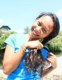Усмехаясь девушка делая косичку Стоковая Фотография