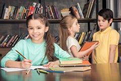 Усмехаясь девушка делая домашнюю работу при одноклассники говоря позади Стоковая Фотография RF