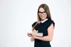 Усмехаясь девушка делая примечания в блокноте Стоковые Фотографии RF