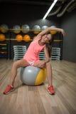 Усмехаясь девушка делая тренировки фитнеса Резвит женщина протягивая на шарике пригонки на предпосылке спортзала Работать концепц Стоковое Фото