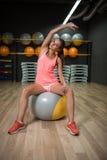 Усмехаясь девушка делая тренировки фитнеса Резвит женщина протягивая на шарике пригонки на предпосылке спортзала Работать концепц Стоковые Фотографии RF
