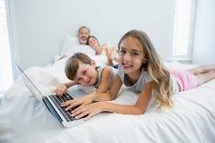 Усмехаясь девушка и мальчик используя компьтер-книжку на кровати в спальне дома Стоковые Изображения RF