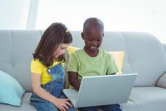 Усмехаясь девушка и мальчик используя компьтер-книжку Стоковые Изображения