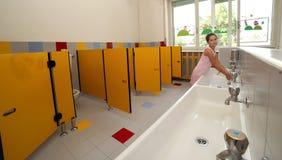 Усмехаясь девушка моя ее руки в ванной комнате школы Стоковая Фотография RF