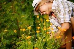 Усмехаясь девушка на предпосылке флористического куста Стоковое Изображение