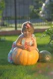 Усмехаясь девушка на pumpking Стоковая Фотография