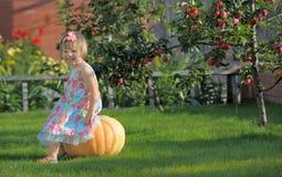 Усмехаясь девушка на pumpking Стоковые Фото