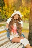 Усмехаясь девушка одела в милой связанной шляпе белого медведя в парке осени стоковые изображения rf