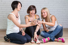 Усмехаясь девушка показывая smartphone Стоковые Изображения