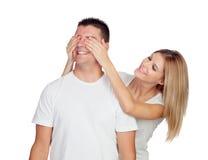 Усмехаясь девушка покрывая глаза его парня для того чтобы удивить его Стоковые Фотографии RF