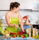 Усмехаясь девушка помогая ее матери подготавливает Стоковое Изображение RF