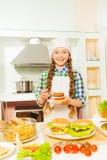 Усмехаясь девушка подготавливая гамбургеры на кухне Стоковые Фотографии RF