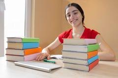 Усмехаясь девушка подростка делая домашнюю работу на таблице дома записывает старую принципиальной схемы изолированная образовани Стоковое Фото