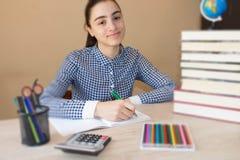 Усмехаясь девушка подростка делая домашнюю работу на таблице дома записывает старую принципиальной схемы изолированная образовани Стоковое фото RF
