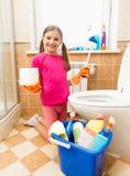 Усмехаясь девушка представляя с туалетной бумагой и щеткой на ванной комнате Стоковая Фотография