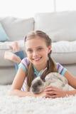 Усмехаясь девушка при кролик лежа на половике в живущей комнате Стоковые Изображения