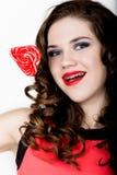 Усмехаясь девушка при расчалки держа конфету сердца представляя на белой предпосылке