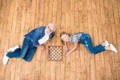 Усмехаясь девушка при старший человек играя шахмат на деревянном поле Стоковая Фотография RF