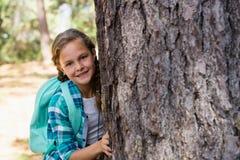 Усмехаясь девушка пряча за деревом Стоковое Фото