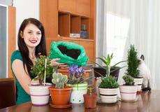 Усмехаясь девушка работая с цветками в баках стоковые изображения rf
