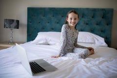 Усмехаясь девушка сидя на кровати в спальне Стоковое Изображение