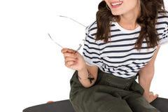 Усмехаясь девушка сидя на скейтборде и держать eyeglasses Стоковые Изображения RF